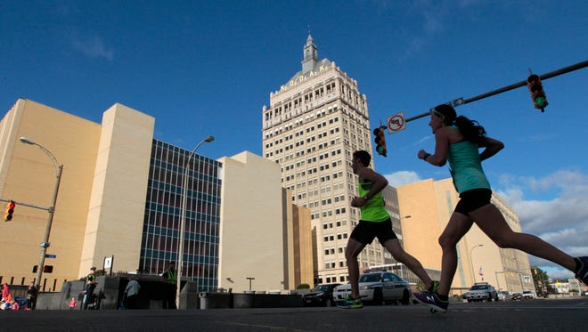 Runners are silhouetted as they pass the Kodak tower and head for the finish line near Frontier Field at the MVP Health Care Rochester Half & Full Marathon Sunday, Sept. 20, 2015 in Rochester.