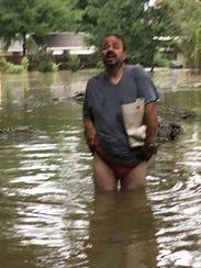 A homeless man navigates the flood near Milton on Aug.