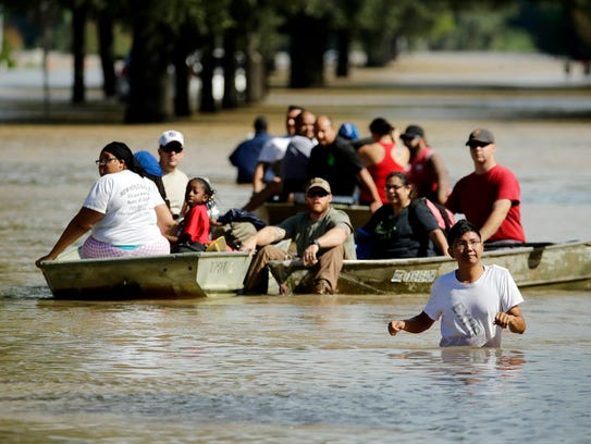 People evacuate a neighborhood inundated after water