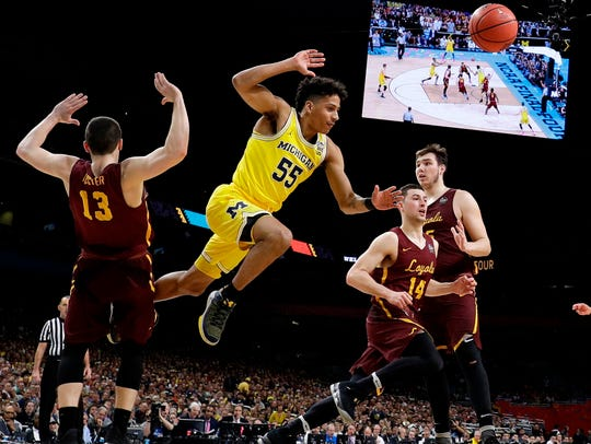 Michigan guard Eli Brooks (55) fights for a rebound