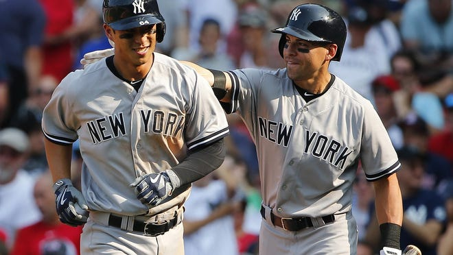 Yankees second baseman Rob Refsnyder celebrates with center fielder Jacoby Ellsbury after hitting a two-run home run during the ninth inning against Boston. Refsnyder will get a chance to win the starting second base job.