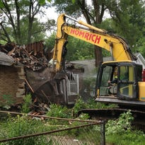 A contracted demolition crew from Detroit-based Homrich demolishes a house on Dolphin Street, as part of the city's blighted house demolition program