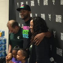 MSU basketball coach Tom Izzo, Morris Peterson and his sister Tonda Peterson-Bryant pose for photos behind Peterson's three daughters Aleena and twins Maliyah and Meilani before the Hoop 4 Water charity game Saturday in Flint.