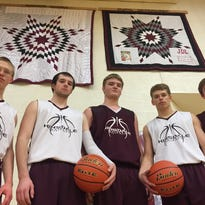Hinsdale senior boys' basketball players Brett Johnson (left to right), Kyle Albus, Lukas Johnson, Dallas Capdeville and Wyatt Pattison pose in front of star quilts hung in the Hinsdale High gymnasium honoring would-be seniors Garrett Younkin and Justin Leatherberry, who were killed in separate car crashes.