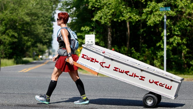 Greta Schwartz of Seaville is dressed like a Spartan warrior pulling a casket as she walks along Route 206 to Trenton Tuesday. Schwartz, who got the idea for the walk after attending a discussion on mental health, addiction and suicide from former U.S. Rep. Patrick Kennedy last year, hopes to arrive at the State House Wednesday.
