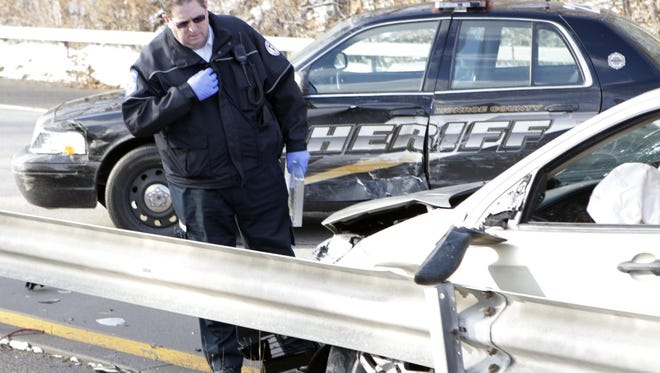 A member of an ambulance crew looks over the damage in December 2007 after a man suspected of shoplifting in Penfield led Monroe County deputies on a short pursuit that ended in a crash. Monroe County has a good record of avoiding fatalities in police chases.