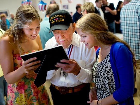 Walter Krupa, a World War II veteran, looks over photographs with his great, great nieces Maddie Nodus-Rydahl, 17, and Paige Nodus-Rydahl, 20, of Mason, during his 100th birthday party Saturday, May 9, 2015 at American Legion Post 525 in Smith's Creek.