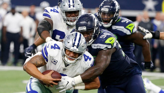 Dallas Cowboys' Dak Prescott (4) is wrapped up by Seattle Seahawks defensive tackle Jarran Reed (90) in the first half of an NFL football game, Sunday, Dec. 24, 2017, in Arlington, Texas.