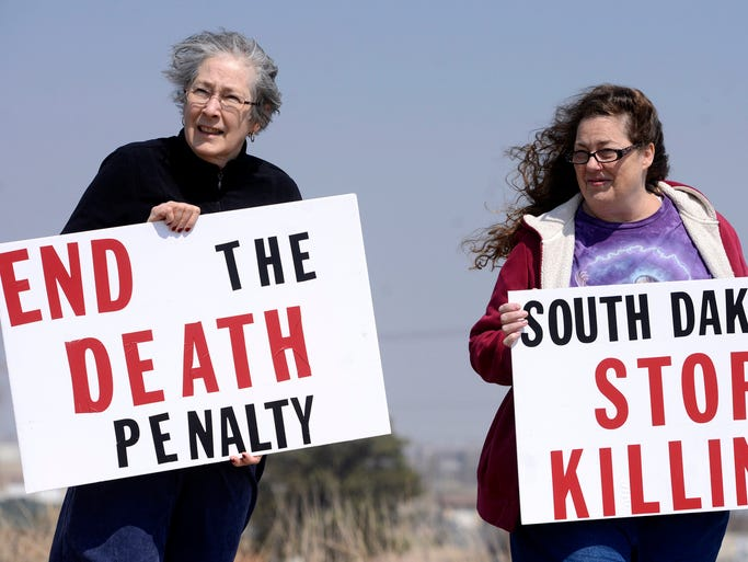 Anne Thompson and Elaine Engelgau hold signs protesting the death penalty Friday following a Good Friday Vigil outside the state penitentiary, April 18, 2014.
