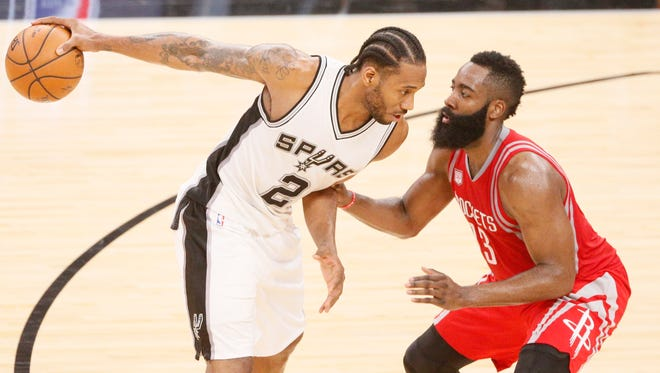 San Antonio Spurs forward Kawhi Leonard is defended by Houston Rockets guard James Harden during the second half at AT&T Center.