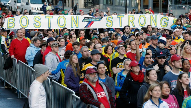 A crowd gathers Saturday at the Boston Marathon finish line for a photo to commemorate the anniversary of the bombings.