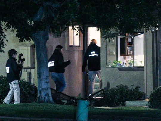 FBI agents search outside a home in connection to the