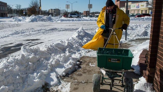 Oscar Diaz lays salt on the sidewalk outside the downtown Salisbury parking garage on Friday.