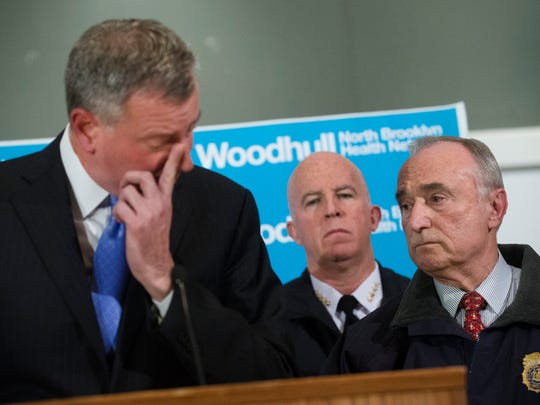 NYPD Commissioner Bill Bratton, right, stands beside Mayor Bill de Blasio as he wipes his eye during a news conference at Woodhull Medical Center, Saturday