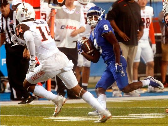 MTSU's Ty Lee (8) runs the ball as Bowling Green's Janarvis Pough (14) moves in for the tackle during the game, on Saturday, Sept. 23, 2017, at MTSU.