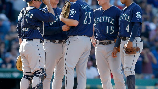 Seattle Mariners manager Scott Servais, second from left, takes the ball from starting pitcher Adrian Sampson as he is surrounded by teammates during the fifth inning of a baseball game against the Boston Red Sox at Fenway Park on Saturday, June 18, 2016, in Boston. (AP Photo/Mary Schwalm)