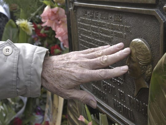 A man touches the tomb of Eva Peron at Recoleta cemetery in Buenos Aires, Argentina.