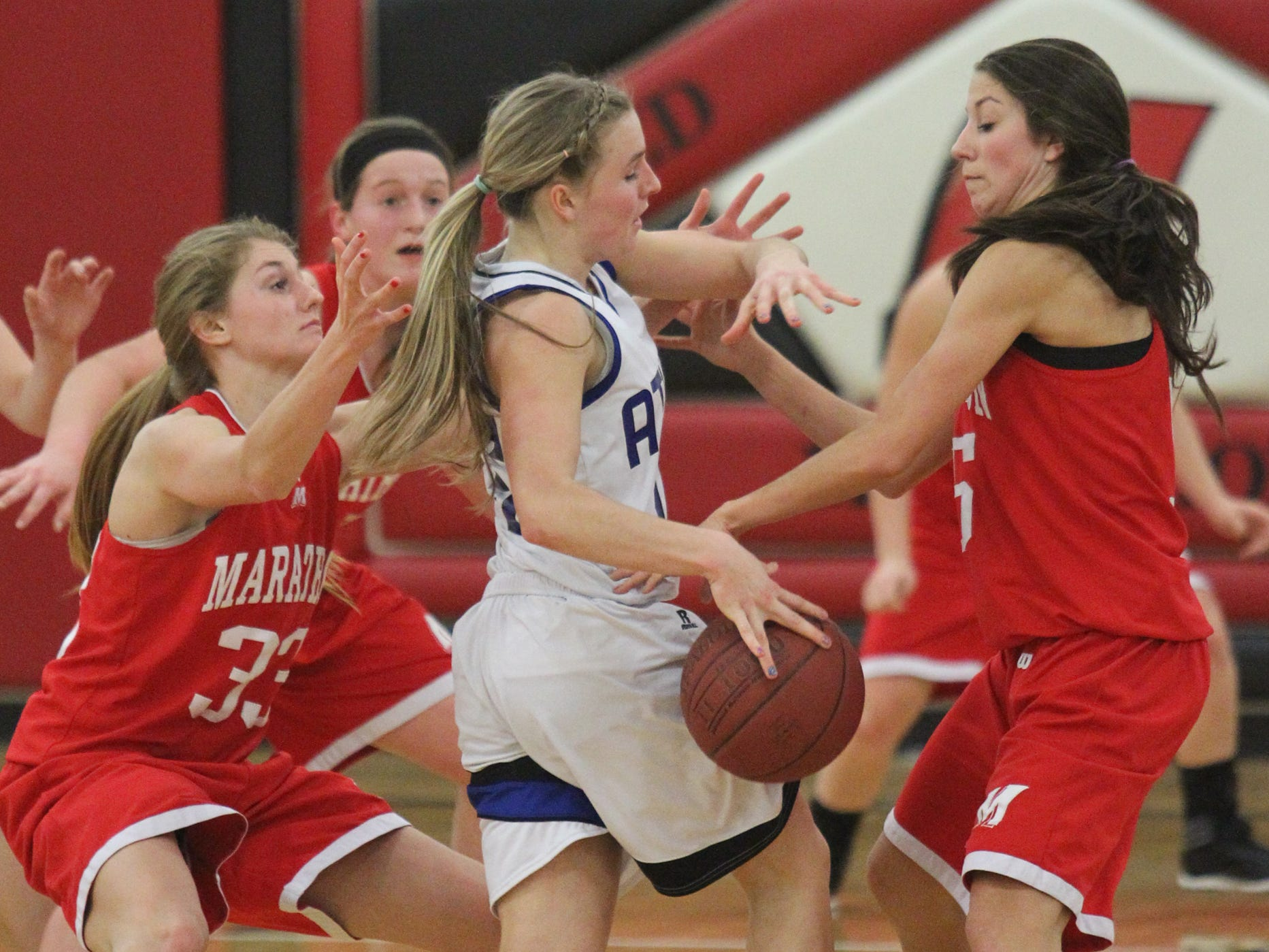 Marathon players surround Athens' Kyncaide Diedrich. Both teams received a No. 1 seed Sunday as the WIAA released the girls basketball brackets.