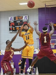LSUA's Chris Vickers (11, center) passes the ball between Loyola University New Orleans defenders Trey LaForge (3, left) and Nick Parker (1, right) Wednesday, Nov. 15, 2017 at the Fort.