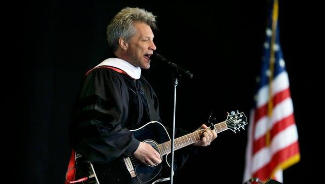 """Rock star and philanthropist Jon Bon Jovi performs a new song during graduation ceremonies at Rutgers University-Camden Thursday, May 21, 2015, in Camden, N.J. The New Jersey native premiered a new song, """"Reunion,"""" which he said was a gift to the graduates. It began, """"This isn't how the story ends, my friends, it's just a fork along the road."""" Bon Jovi and Bryan Stevenson, public interest lawyer and founder and executive director of the Equal Justice Initiative, received honorary degrees."""