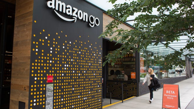 A woman walks past the Amazon Go grocery store at the Amazon corporate headquarters in June in Seattle.