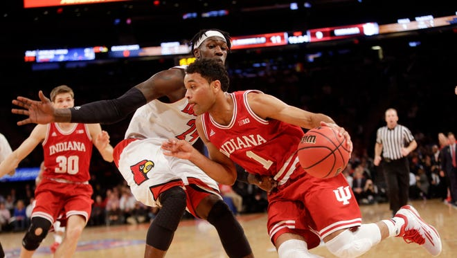 Indiana's James Blackmon Jr. (1) drives past Louisville's Montrezl Harrell (24) during the first half of an NCAA college basketball game Tuesday, Dec. 9, 2014, in New York. (AP Photo/Frank Franklin II)