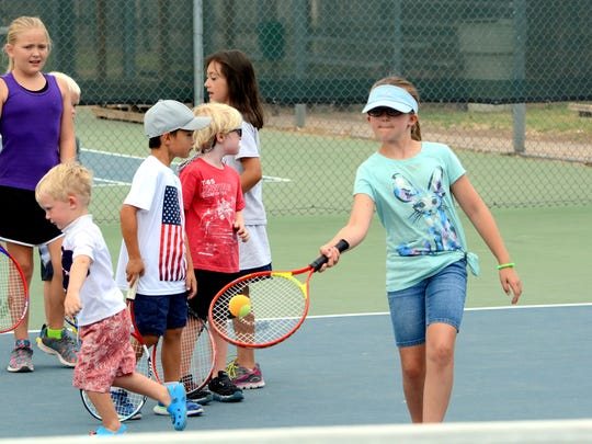 Lily Yost, 9, works on her forehand swing Friday at
