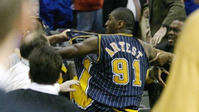 Indiana Pacers forward Ron Artest is grabbed by fans after he went into the seats during a a brawl with the Detroit Pistons with just 45.9 seconds left in the game Friday, Nov. 19, 2004, in Auburn Hills.