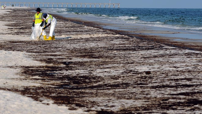 Crews work to clean up oil from the Deepwater Horizon disaster along Pensacola Beach in June 2010.