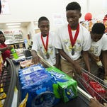 Kendarrius Jones, from left, Roderious Harmon and Christopher Thornton helps a customer unload groceries as the Zulu Warring Hornets basketball team raises money, by bagging groceries at the Cash Saver on the South Boulevard in Montgomery on Friday to go to the National Junior Olympics in Lincoln, Nebraska.