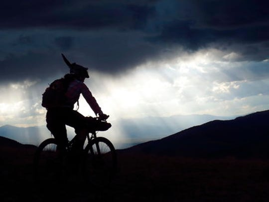 In this Aug. 14, 2014 photo provided by Scott Morris, Eszter Horanyi rides with a storm backdrop, along the Continental Divide Trail in Montana.