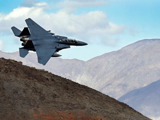In this Feb. 27, 2017, photo an F-15E Strike Eagle from Seymour Johnson AFB in North Carolina flies out of the nicknamed Star Wars Canyon turning toward the Panamint range over Death Valley National Park, Calif. Military jets roaring over national parks have long drawn complaints from hikers and campers. But in California's Death Valley, the low-flying combat aircraft skillfully zipping between the craggy landscape has become a popular attraction in the 3.3 million acre park in the Mojave Desert, 260 miles east of Los Angeles.
