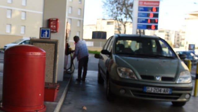 A consumer fills up his fuel tank at a gas station on December 26 in Marseille, southeastern France. Oil prices have fallen about 50 percent since June on mounting supplies due to increased production and lackluster global economic growth.