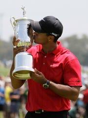 Tiger Woods kisses his U.S. Open championship trophy
