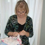 Susan Kisinger with some of the pillowcases donated to her group that makes dresses for children in Haiti.