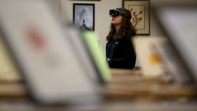 Madison Sloniker, 14, looks around the library while wearing an augmented reality headset as she and fellow students try out augmented and virtual reality devices courtesy of Microsoft at Kingston High School on Friday.