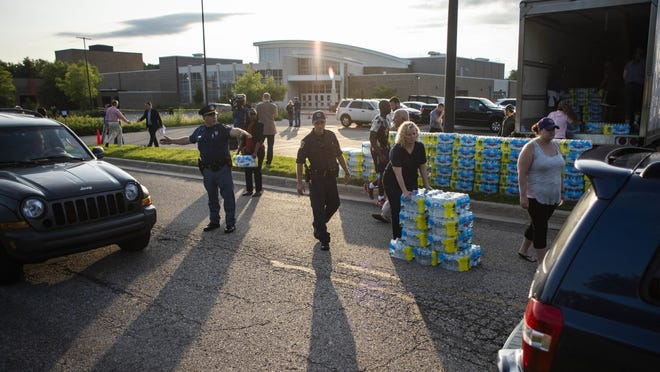 Emergency response teams hand out bottled water to residents at Parchment High School in Parchment, Michigan, on July 27, 2018. Authorities handed out the bottled water in the Kalamazoo County community and Cooper Township after the discovery of high levels of industrial chemicals were discovered in the water systems.