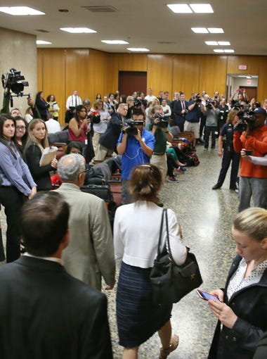 Laura Rideout, bottom center in white sweater, walks with her lawyers, Michael DiPrima, left, and David Pilato, bottom, past a crowd of onlookers and media as they head into court for the verdict in the Craig Rideout murder trial.  Laura Rideout was found guilty of second-degree murder, burglary and tampering with evidence.