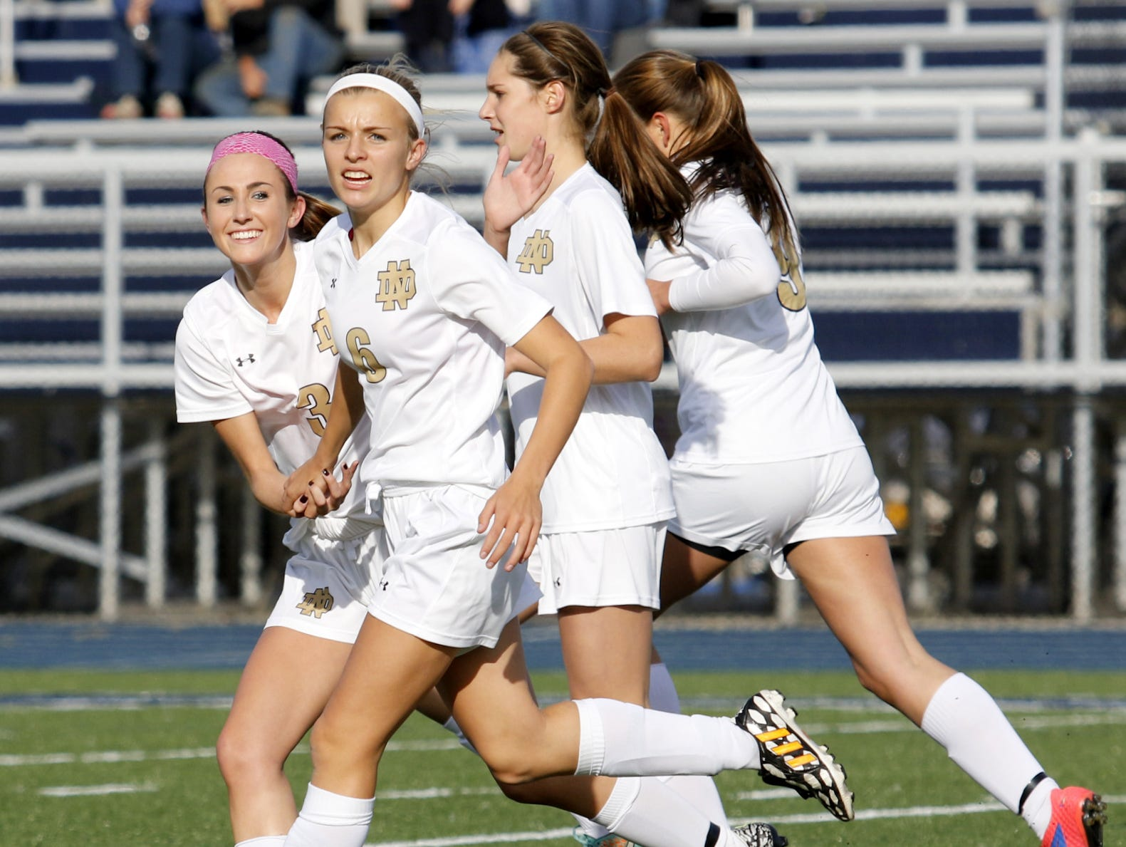 Notre Dame players, from left, Reilly Edger, Maura Glovins, Camille VanderMeer and Mackenzie Mahajan celebrate Glovins' first-half goal Tuesday during a 2-0 win over Trumansburg in a Section 4 Class C girls soccer semifinal at Brewer Memorial Stadium.