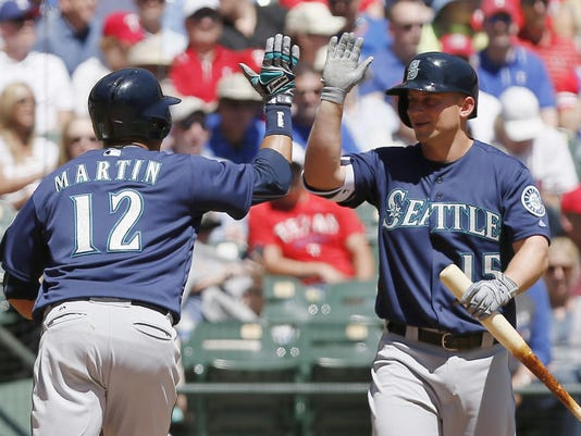 Seattle Mariners' Leonys Martin (12) is congratulated by Kyle Seager (15) after hitting a solo home run during the second inning of a baseball game against the Texas Rangers Wednesday, April 6, 2016, in Arlington, Texas. (AP Photo/Brandon Wade)
