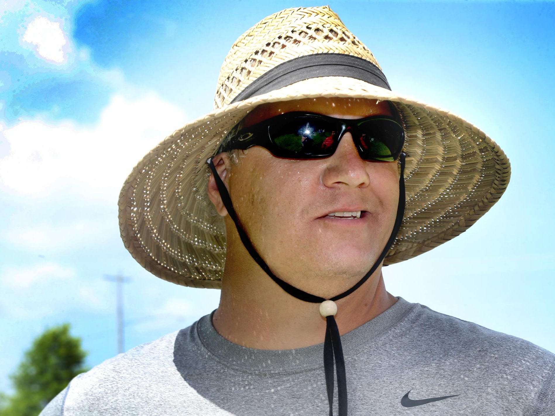 David Watson, the new head coach of the Blackman High School football team, tries to stay cool and out of the sun under his big straw hat as the Blackman Blaze competes in the 7-on-7 Bojangles Passing Tournament on Thursday, July 9 at Riverdale High School in Murfreesboro.