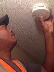 A fire official installs and tests a new smoke detector.