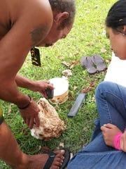 Co-instructor, expert toolsmith and craftsman Joe Viloria, demonstrating how to use alutong gachai (basalt adze) with student Tamara Manglona