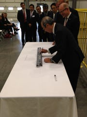 Shinya Ogawa, president, Pacific Industrial Co., signs