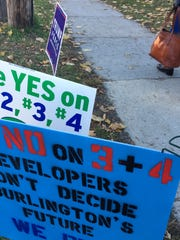 Competing messages: Signs posted Tuesday at Edmunds MIddle School urge Burlington voters to oppose or support ballot items that would advance redevelopment plans for the city's downtown mall. Photographed Nov. 8, 2016.