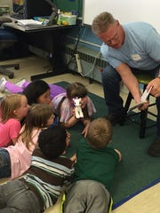 Rothschild Elementary second- and third-graders enjoying a chapter book with a Domtar volunteer.