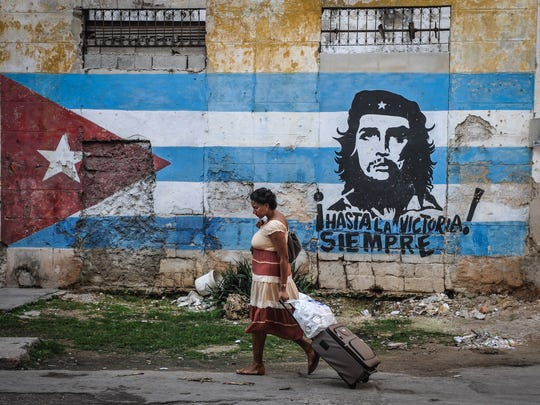 """A woman walks by a mural with the Cuban flag and an image of revolutionary leader Ernesto """"Che"""" Guevara, in Havana on January 23, 2015."""