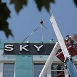 Workers install a new sign at the top of the former Woodruff building at Jefferson Avenue and St. Louis Street on Monday. The 90-unit apartment building, Sky Eleven, will be ready for residents to move in on August 7.