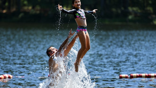 Gia Rodriguez, 8, launches form her dad's shoulders in the swimming area of Rutland Sate Park.