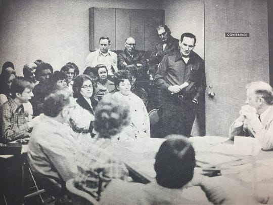 Caseyville mayor Willford Allen (pictured next to the door) spoke to members of the Union County Board of Education concerning a proposal for construction of a coal loading dock on the Ohio in February 1975. Seated in the background are residents of Caseyville and bus drivers employed by the Union County Board of Education.
